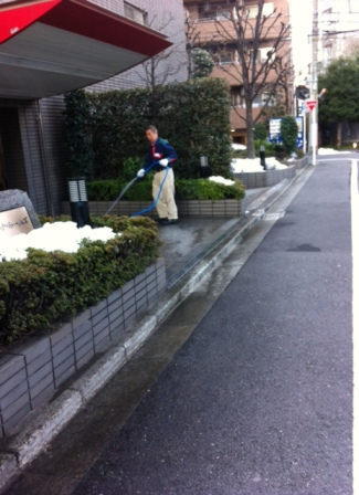 An apartment building caretaker attempts to hose away the last of the offending snow.