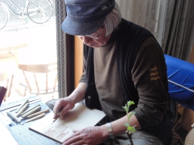 This man is a local artist; he is carving a woodblock to make woodblock prints.
